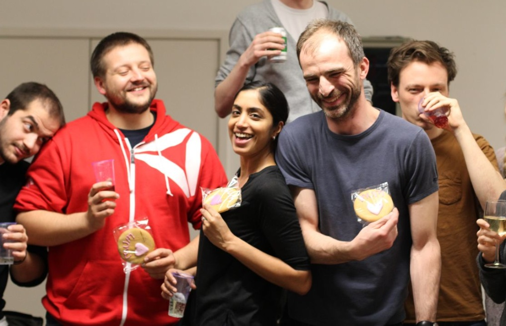 group of laughing individuals holding biscuits